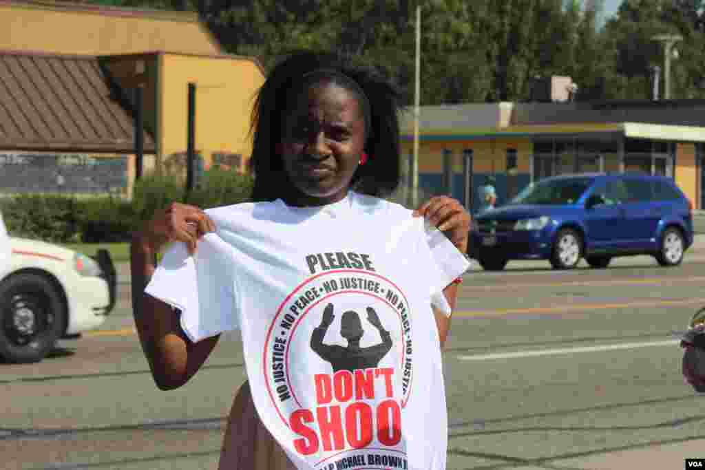 A woman holds up a tee shirt referring to the shooting of unarmed African American teenager Michael Brown, Ferguson, Missouri, Aug, 24, 2014. (Gesell Tobias, VOA)