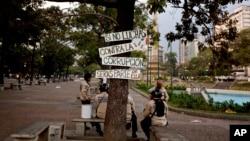 Miembros de la guardia bolivariana descansan a la sombra de un árbol con rótulos anticorrupción en Caracas.