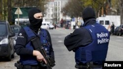 Belgium police officers secure the access during a police operation in Etterbeek, near Brussels, Belgium, April 9, 2016.