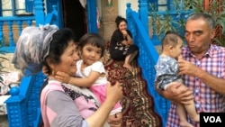 A Uyghur man and woman hold young Uyghur children in Xinjiang, China (VOA)