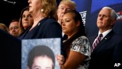 Prezidan Donald Trump ki t ap koute pandan yon rankont sou imigrasyon. Li te genyen bò kote li manm fanmi moun ki te viktim krim imigran ilegal komèt Ozetazini. (Oditoryòm Sid Mezon Blanch la, 22 jen 2018 la, nan Washington).