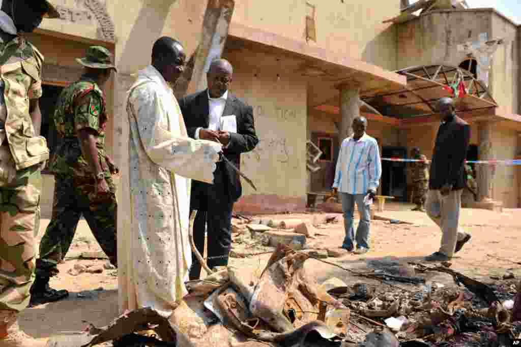 A member of the clergy guides security forces through the scene of a car bomb explosion at St. Theresa Catholic Church outside Nigeria's capital Abuja. (Reuters)