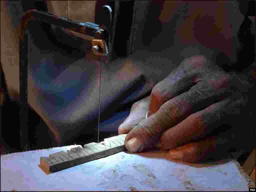 محمد علی لکڑی کے چھوٹے چھوٹے ٹکڑوں پر انگریزی حروف میں نام لکھنےکا فن رکھتے ہیں۔