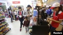 Nhân viên kiểm tra hóa đơn của khách hàng tại một siêu thị ở Hà Nội.