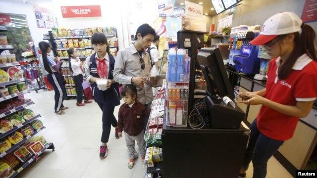 Nhân viên kiểm tra hóa đơn của khách hàng bên trong siêu thị ở Hà Nội, ngày 12/10/2015.