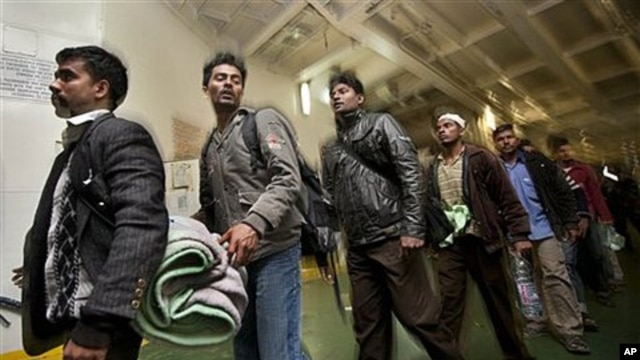 Some of the 1,200 migrant workers who were evacuated from Misrata by boat, many suffering from dehydration and needing medical attention, leave the boat after it arrived at the port in Benghazi, Libya, April 15, 2011