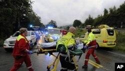 图为救护人员正把伤者从夏令营抬走