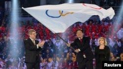 International Olympics Committee President Thomas Bach, left, applauds as Pyeongchang Mayor Lee Sok-ra, second right, waves Olympic flag during the closing ceremony for Sochi 2014 Winter Olympics, Feb. 23, 2014.