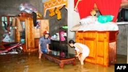 Cư dân dời đồ đạc trong căn nhà bị ngập lụt ở tỉnh Quảng Bình, miền Trung Việt Nam, 18/10/2011
