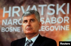 FILE - Newly elected President of Croatian National Parliament and President of HDZ political party (Croatian Democratic Union) Dragan Covic listens during a news conference after a meeting in Mostar, April 19, 2011.