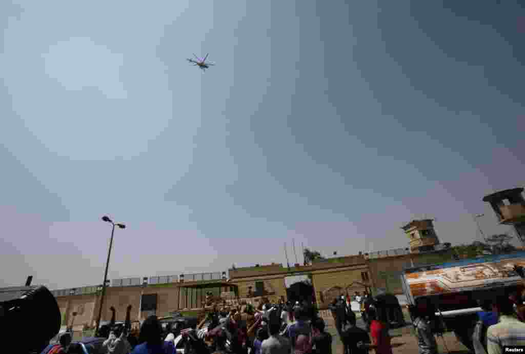 Supporters of deposed Egyptian president Hosni Mubarak gesture as the helicopter carrying him leaves Tora prison, Cairo, August 22, 2013.