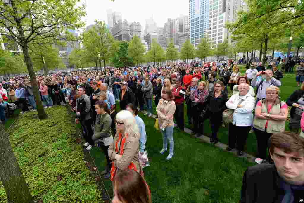 Members of the public watch a projection screen at the World Trade Center Plaza during the dedication ceremony of the National September 11 Memorial Museum, New York City, May 15, 2014.