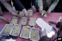 Volunteers of the soup kitchen ''O Allos Anthropos'' (The other Man) deliver free food for all at Monastiraki square in central Athens, April 25, 2017.