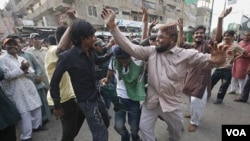 Warga pendukung partai politik relijius Sunni berdansa dengan iringan lagu nasional Pakistan dalam demonstrasi anti-Amerika di Karachi (28/9).