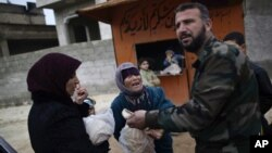 A woman asks a Free Syrian Army fighter to sell her bread, in Maaret Misreen, near Idlib, Syria, December 13, 2012.