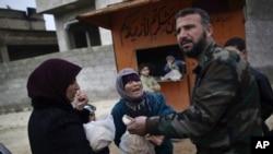 지난달 13일 시리아 이들립시에서 반군에게 빵을 팔아달라고 부탁하는 여성들.
