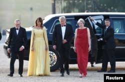 U.S. President Donald Trump and first lady Melania Trump are met by British Prime Minister Theresa May and her husband, Philip, at Blenheim Palace, where they are attending a dinner with other specially invited guests and business leaders, near Oxford, July 12, 2018.