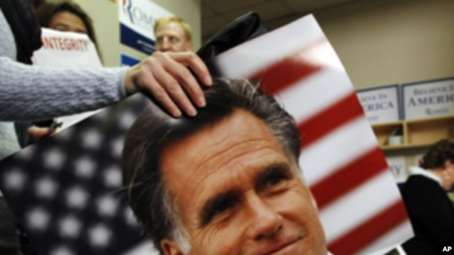 A supporter of U.S. Republican presidential candidate and former Massachusetts Governor Mitt Romney carries a photo of Romney past a campaign worker calling potential voters in Greenville, South Carolina, January 21, 2012.
