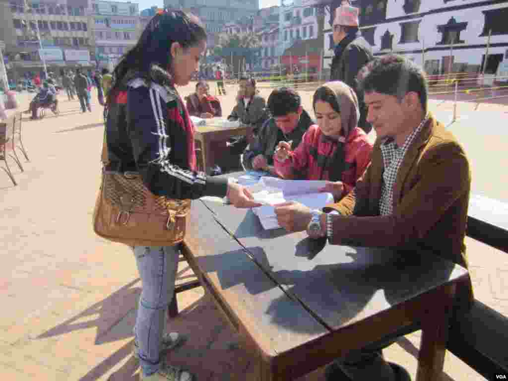 A woman collects her election identification card in Durbar Square, Kathmandu, Nov. 17, 2013. (Aru Pande/VOA)