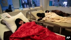 FILE - Women are treated for a suspected cholera infection at a hospital in Sana'a, Yemen, May 15, 2017.