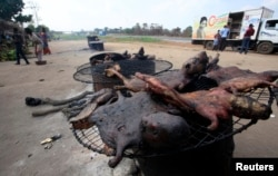 People walk near dried bushmeat near Yamoussoukro highway in Ivory Coast on March 29, 2014.