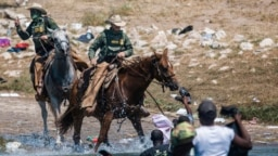 US Customs and Border Protection mounted officers attempt to contain migrants as they cross the Rio Grande from Ciudad Acuña, Mexico, into Del Rio, Texas, Sept. 19, 2021.
