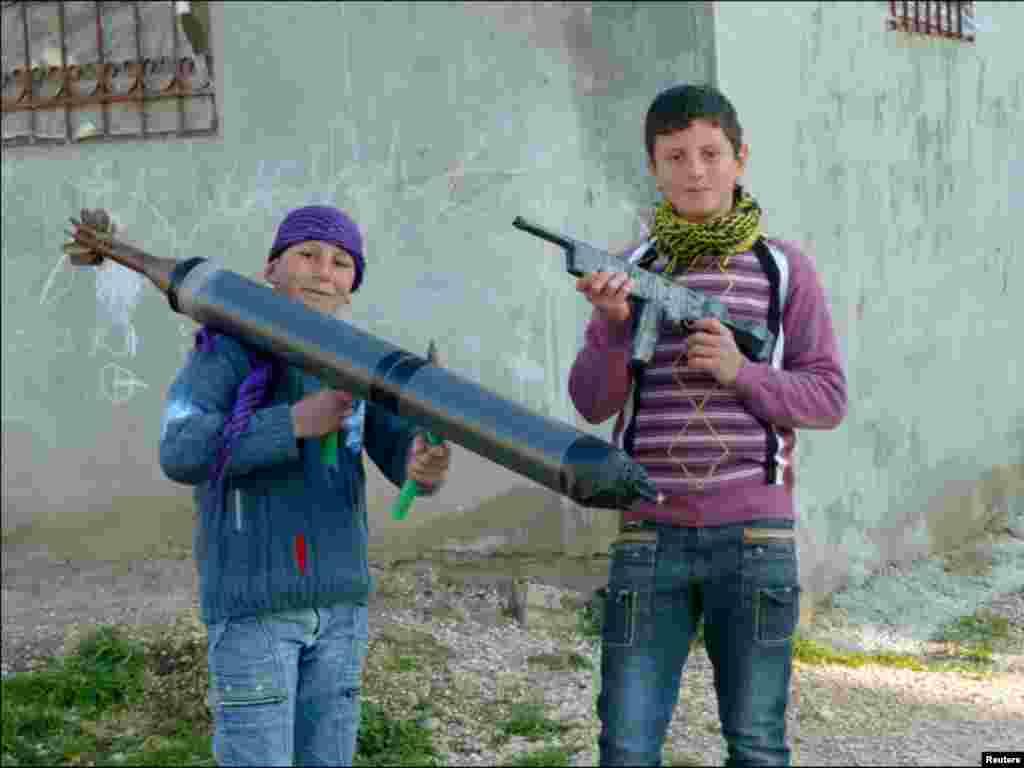 سائیریا کے شہر میں دو بچے کھلونا ہتھیار لئے ہوئے ہیں۔
