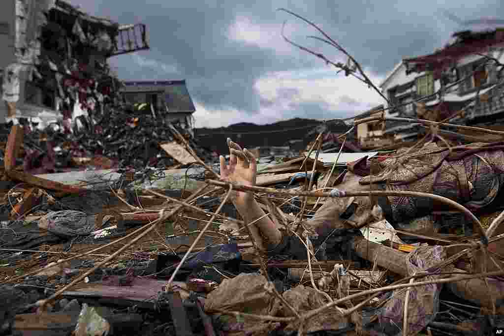 The arm of a mannequin sticks out from the rubble in a devastated neighborhood in Kesennuma, Miyagi prefecture, in northeastern Japan, May 30, 2011. (AP)