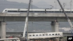 图为7月26日高速列车在曾经出事的高架桥上驶过,桥下的现场正在清理中