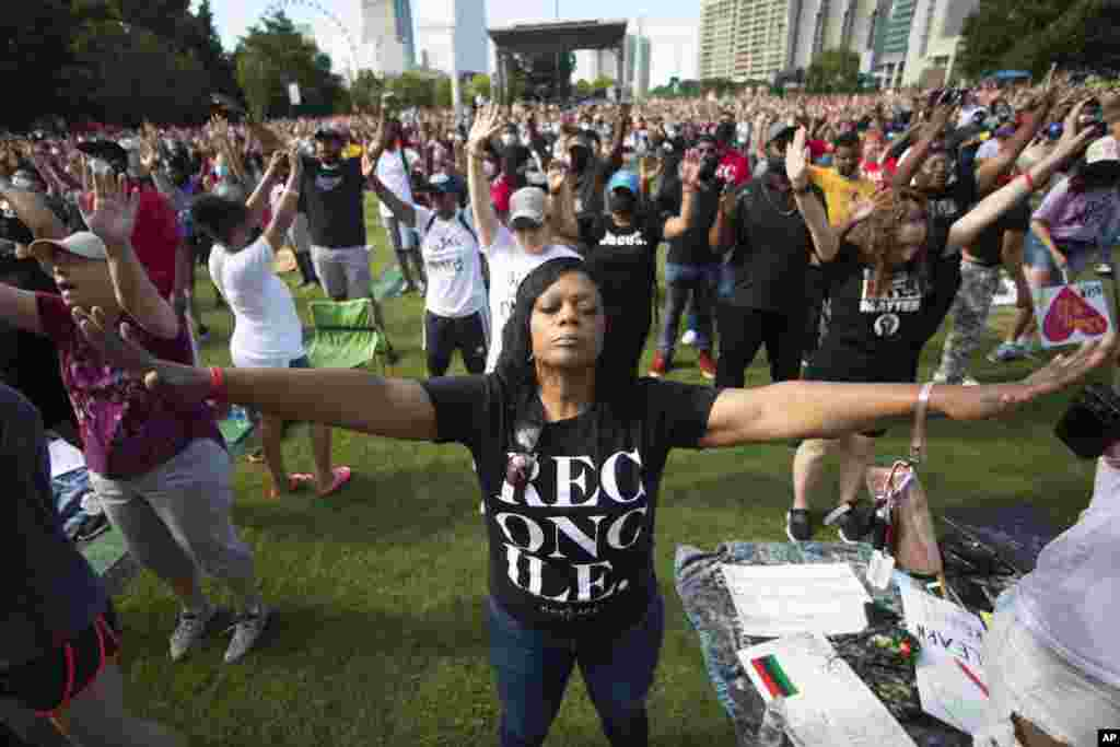 A woman prays during an event hosted by OneRace Movement at Atlanta's Centennial Olympic Park to commemorate Juneteenth, the date of the emancipation of enslaved African Americans in the U.S.