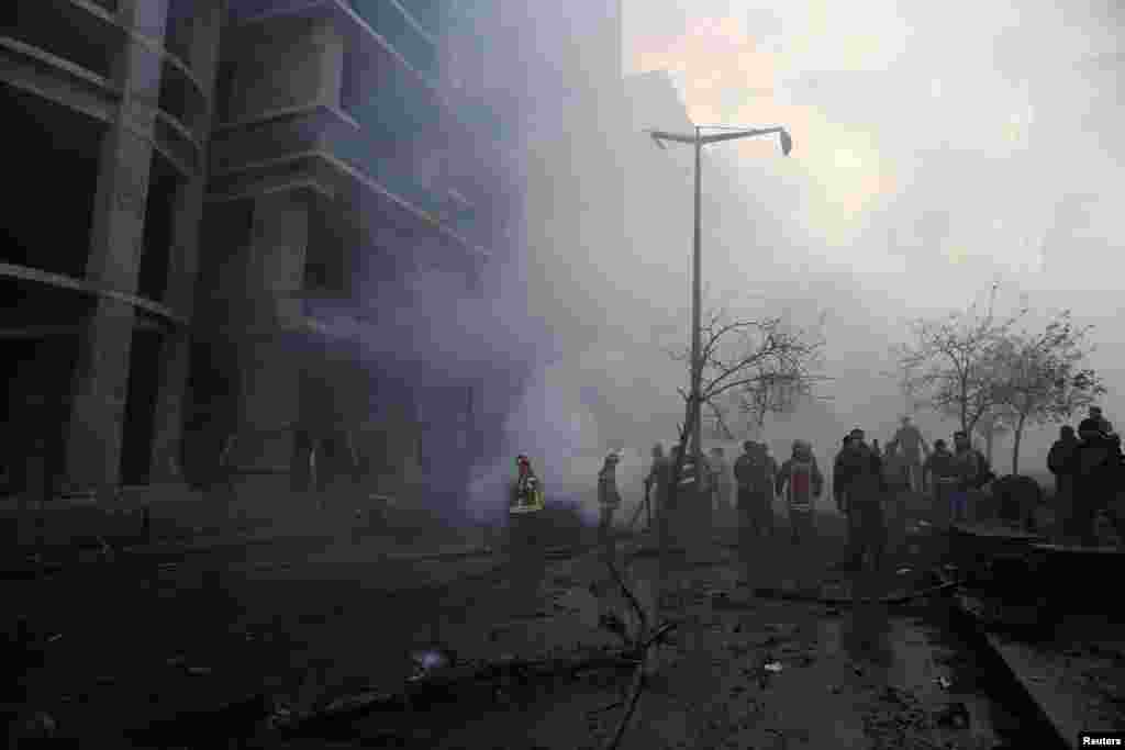 Fire fighting and army personnel inspect the site of an explosion in Beirut's downtown area, Dec. 27, 2013.