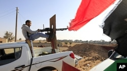 一名利比亚反政府组织成员用重机枪瞄准利比亚领导人卡扎菲的支持者