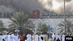 Warga Oman menyaksikan asap mengepul dari sebuah toserba di Sohar, Senin (28/2).