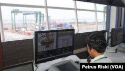 Pengoperasian peralatan bongkar muat peti kemas dengan crane bertenaga listrik dan dikendalikan operator dari ruang kontrol di Terminal Teluk Lamong Surabaya (VOA/Petrus Riski)