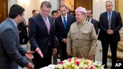 U.S. Defense Secretary Ash Carter gestures to the guest book he just signed as he stand with Kurdish regional government President Massoud Barzani at the White House in Irbil, Iraq, July 24, 2015.