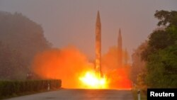 지난달 21일 북한 조선인민군 전략군 화성포병부대가 탄도미사일 발사훈련을 실시했다며, 관영 조선중앙통신이 공개한 사진. 앞쪽에는 스커드 미사일이 발사되고 있고, 뒤쪽에는 '노동'으로 추정되는 미사일 2기가 발사 준비 상태에 있다. (자료사진)