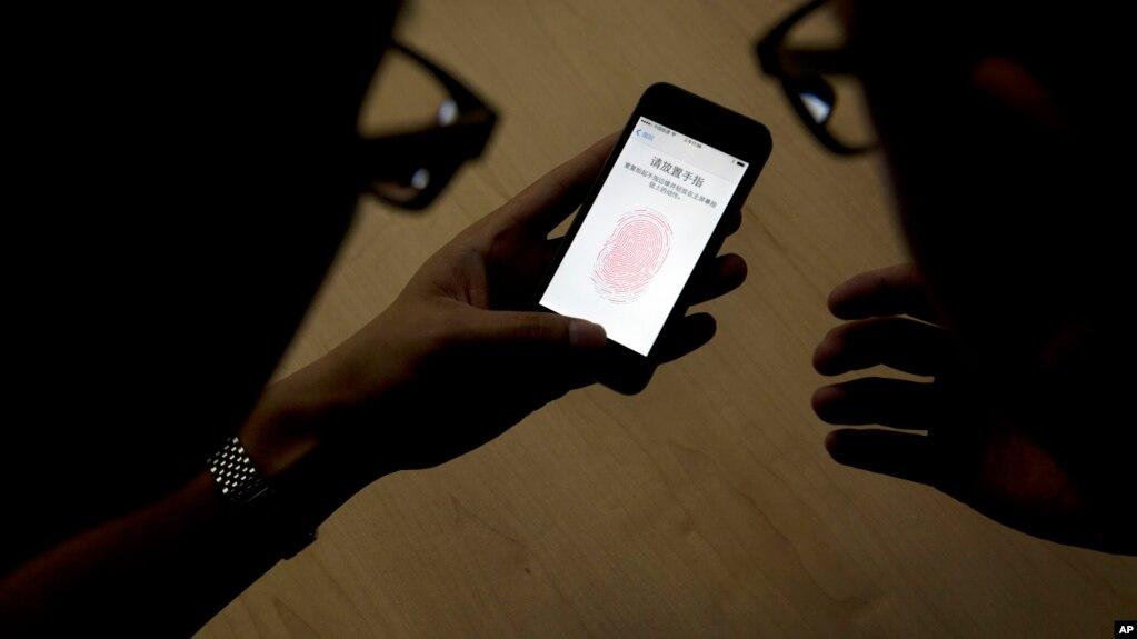 2013年9月11日苹果公司员工在中��北京向�者介�BiPhone 5S�戎弥肝�呙杓夹g。
