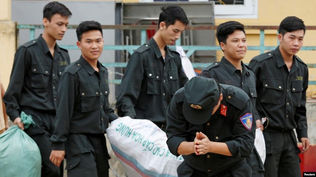 Một cảnh sát cúi đầu cảm tạ dân làng Đồng Tâm sau khi được phóng thích hôm 22 tháng Tư. (Hình: REUTERS/Kham)