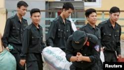 Một cảnh sát cơ động cúi lạy người dân làng Đồng Tâm sau khi được thả ra vào ngày 22/4/2017.
