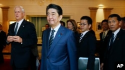 Japanese Prime Minister Shinzo Abe, center, tours the John F. Kennedy Presidential Library in Boston, with Edwin Schlossberg, left, and Caroline Kennedy, background center, Sunday, April 26, 2015.