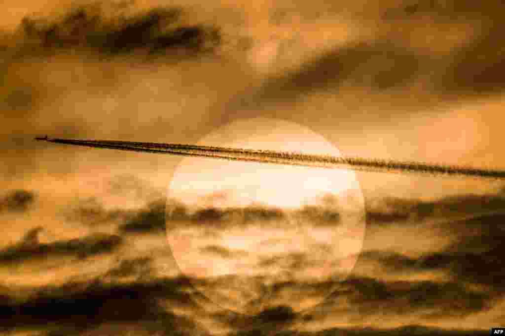 A passenger plane flies past the sun in Yangon, Myanmar.