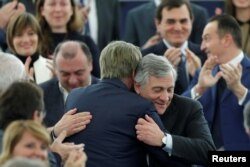 Newly elected European Parliament President Antonio Tajani is congratulated by members of the Parliament, Jan. 17, 2017.