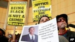 Anita ross sostiene una foto de Stephon Alonzo Clark, durante una protesta a la entrada de Sacramento, el jueves 22 de marzo de 2018. Clark murió tiroteado por policías de la ciudad que respondieron a una denuncia contra un hombre que estaba destruyendo vehículos.