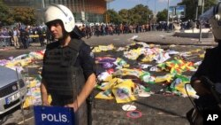 Bodies of victims are covered with flags and banners as a police officer secure the area after an explosion in Ankara, Turkey, Oct. 10, 2015.
