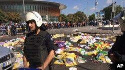Jenazah korban bom ditutup dengan bendera dan spanduk sementara polisi mengamankan lokasi setelah terjadi insiden ledakan di Ankara, Turki (10/10).