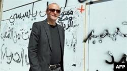 Đạo diễn Mourad Cheikh của Tunisia đi dọc theo bức tường có vẽ chữ ở thành phố Tunis