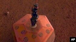 Esta foto facilitada por el Laboratorio de Propulsión a Chorro de la NASA muestra un sismógrafo colocado en suelo de Marte por la sonda InSight. La sonda colocó el dispositivo el miércoles 19 de diciembre de 2018.