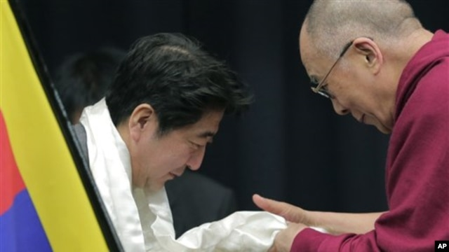 Tibetan spiritual leader the Dalai Lama, right, gives a white Tibetan scarf  to Japan's main opposition Liberal Democratic Party President Shinzo Abe during a seminar held by Japanese Diet members in Tokyo, Tuesday, Nov. 13, 2012.  (AP Photo/Itsuo Inouye)