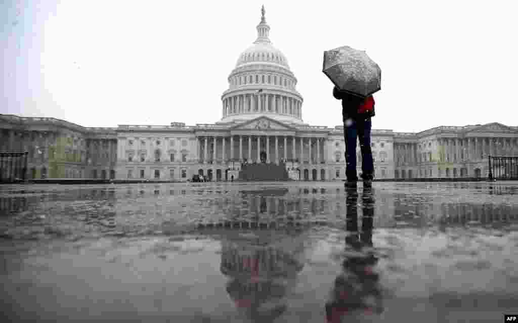 2013年3月6日,華盛頓雨雪交加,一位遊客在美國國會山附近打傘遮蔽雨雪。