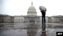 И снег, и дожд: еден од ретките туристи средата наутро пред зградата на Конгресот на Капитол Хил, на почетокот на големото зимско невреме што го зафати Вашингтон